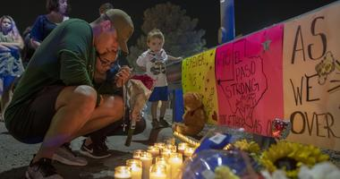 people mourn at a vigil after a shooting in an El Paso Walmart