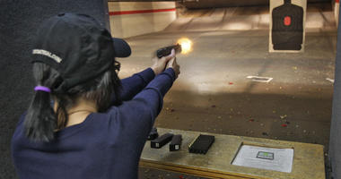 Woman fires a gun in a shooting range.