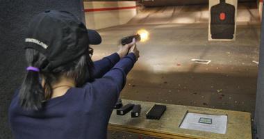 Woman fires a gun in a shooting range.
