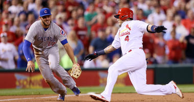 St. Louis Cardinals' Yadier Molina (4) slides safely into third base with an RBI triple ahead of Chicago Cubs third baseman Kris Bryant