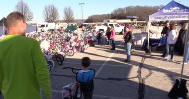 Young man and his grandpa walk their bike over to be donated.