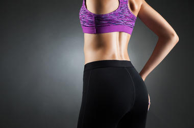 Fit sportswoman with in black yoga pants and purple top, back view. Studio portrait black background.