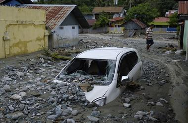 A car sits abandoned in the mud on a flooded street on March 20, 2019 in Sentani, Papua province, Indonesia. At least 104 people have died and nearly 7,000 have been displaced from their homes after three straight days of heavy rain led to massive flash