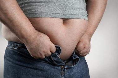 Overweight man trying to wear too small jeans