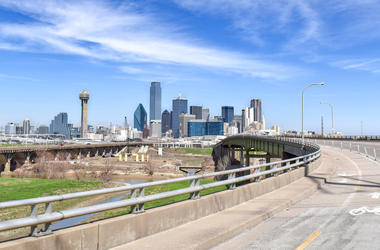 Wide shot of Highway Overpass with Trinity River and Skyline of Downtown Dallas in the Distance on a Clear Summer Day - Dallas, Texas, USA