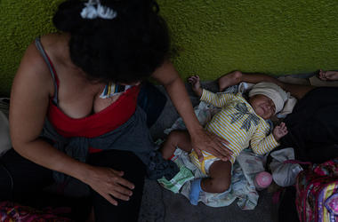 A Honduran migrant and her baby take shelter on a sidewalk on June 19, 2019 in Tapachula, Mexico. Since shelters in the city are over capacity, many migrants are living on sidewalks while they wait for their appointments to obtain a humanitarian visa.