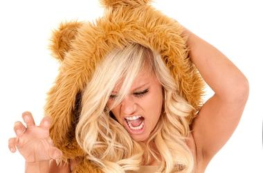 A woman dressed like a lion with her hand like claws.