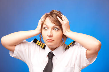 Worried woman pilot wearing uniform with epauletes looking ahead, standing on blue background