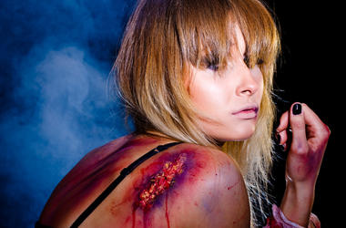 Bruised and wounded woman who survived after a tough fight; studio shot