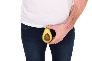 Man is holding avocado, isolated on white background.