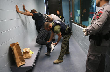 U.S. Immigration and Customs Enforcement (ICE), agents frisk a detained immigrant at a processing center on October 14, 2015 in Camarillo, California. ICE builds deportation cases against thousands of both undocumented and Green Card holding immigrants co