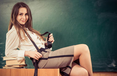 young sexy lady sitting at classroom blackboard background