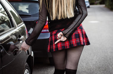 Sexy blond girl keying black car.