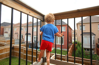 Little boy standing on the balcony (patio) above the ground and trying to climb on balcony railing. House living and child-proofing