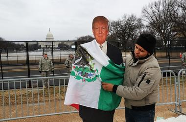 Tony Cervantes, a Zapatista activist who is against President Donald Trump, places a Mexican flag on a Trump cut-out on the National Mall following the inauguration of President Trump on January 20, 2017 in Washington, DC. Washington and the entire world