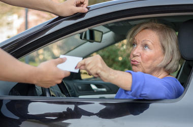 Concerned elderly woman driver handing over her licence to a man reaching towards the open window during a road block or after committing a minor offence