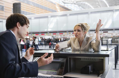 Upset businesswoman checking in at airport ticket counter