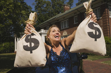 Woman with money bags in front of mansion - stock photo
