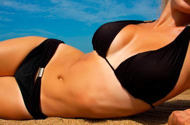 A woman sunbathes on a beach. Slim, female.