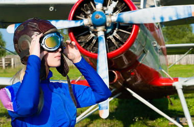 Woman pilot in helmet on background of airplane outdoors