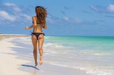 Hispanic Brunette Model Running On The Beach