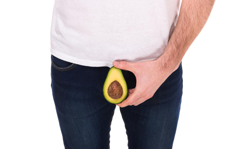 Man is holding avocado, isolated on white background.