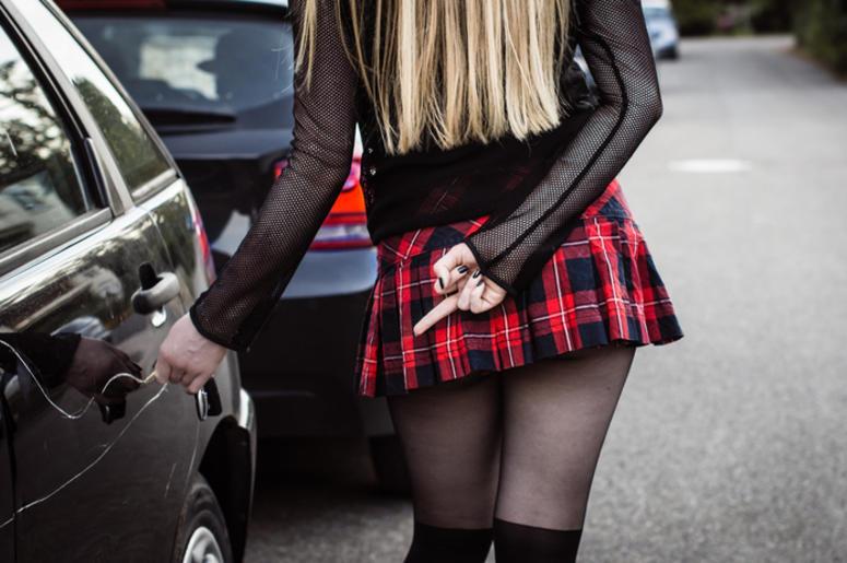 Sexy blond girl keying black car.
