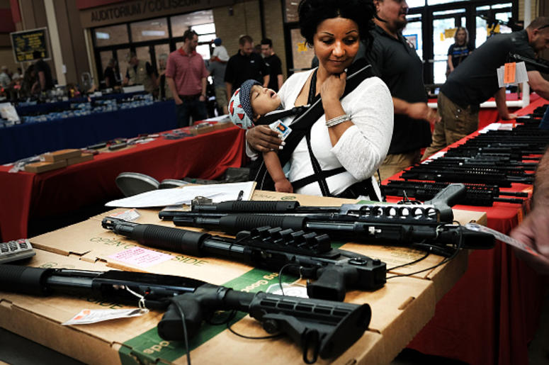 A woman admires weapons at a gun show where thousands of different weapons are displayed for sale on July 10, 2016 in Fort Worth, Texas. The Dallas and Forth Worth areas are still mourning the deaths of five police officers last Thursday evening by a lone