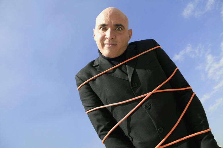 Low angle view of a mid adult man tied up in rope