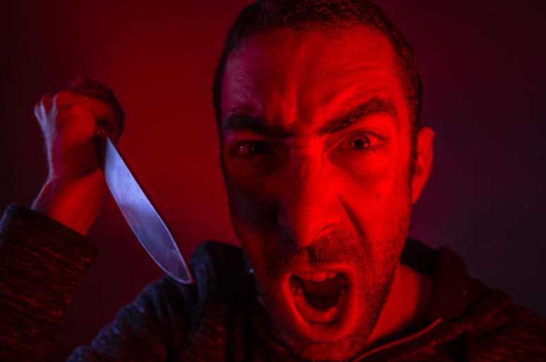 Aggressive man screaming out loud and swinging a knife. Close up portrait of a man with angry facial expression.