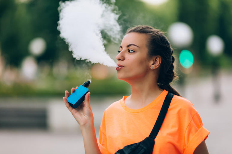 Pretty young girl vape popular ecig gadget,vaping device.Happy brunette vaper girl with e-cig.Portrait of smoker female model with electronic cigarette vaporizer.Ejuice vaping with fruit flavor liquid