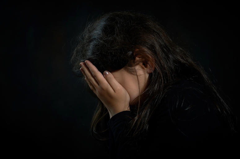 Portrait of a crying girl. She is covering her face.