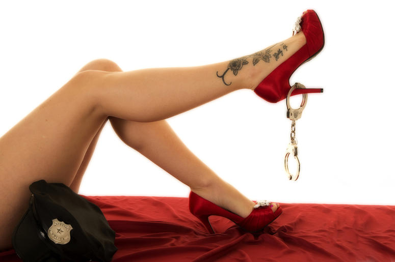 Woman legs in red shoes with handcuffs and a tattoo