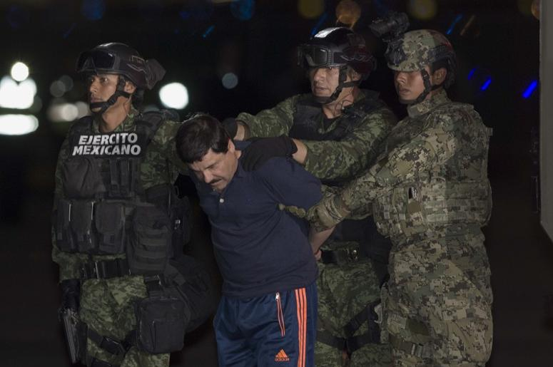 """Soldiers escort Joaquin Guzman Loera, alias """"El Chapo"""", upon his arrival to the hangar of the Attorney General's Office, in Mexico City, capital of Mexico, on Jan. 8, 2016. After an early morning raid in northwestern Mexico's Sinaloa State's town of Los"""