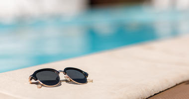 sunglasses by the pool on a sunny summer day