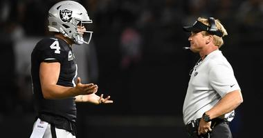 Derek Carr and Jon Gruden try to get on the same page during an Oakland Raiders game in 2018.