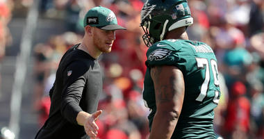 Carson Wentz and Brandon Brooks slap hands during a Philadelphia Eagles game in 2018.