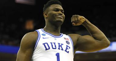 Zion Williamson of Duke flexes and smiles during a game against North Carolina.
