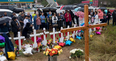 Nov 12, 2017; Sutherland Springs, TX, USA; A large group of people sing around a makeshift memorial honoring the First Baptist Church shooting victims on Sunday, Nov. 12, 2017.