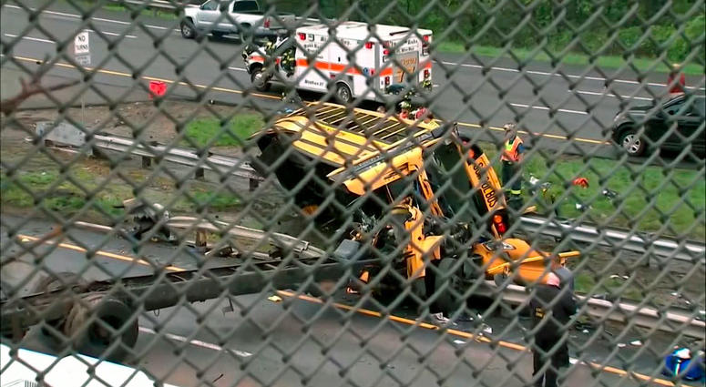This image taken from WABC-TV video shows an overturned school bus after it collided with a dump truck, injuring multiple people, on Interstate 80 in Mount Olive, N.J.