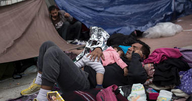 A migrant father and child, who traveled with the annual caravan of Central American migrants, rest where they set up camp to wait for access to request asylum in the US, outside the El Chaparral port of entry building at the US-Mexico border in Tijuana,