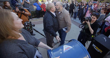 Mark Lindsay, left, and Tom Kerns kiss after mailing a resignation letter as Mormons gather for a mass resignation from the Church of Jesus Christ of Latter-day Saints Saturday, Nov. 14, 2015, in Salt Lake City. A day after the Mormon church stood behind