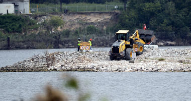 In this Sept. 13, 2017, file photo, workers are shown at San Jacinto River Waste Pits near the Interstate 10 bridge over the river in Channelview, Texas. Federal environmental regulators have reached a long-awaited agreement with the owners of a polluted