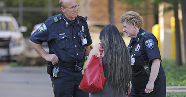 Law enforcement officers stand guard at the driveway entrance to the emergency room at Presbyterian Hospital in Dallas.