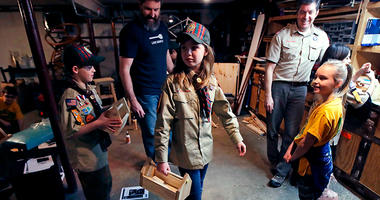 """FILE - In this March 1, 2018, file photo, Tatum Weir, center, carries a tool box she built as her twin brother Ian, left, follows after a Cub Scout meeting in Madbury, N.H. Fifteen communities in New Hampshire are part of an """"early adopter"""" program to all"""