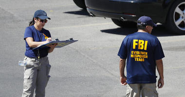 Members of the FBI evidence response team investigate the scene of a mass shooting at a shopping complex Sunday, Aug. 4, 2019, in El Paso, Texas.