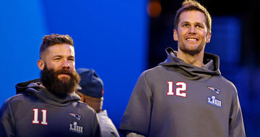 Tom Brady and Julian Edelman of the New England Patriots smile on stage before Super Bowl LIII.