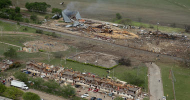 File Photo: Search and rescue workers comb through what remains of a 50-unit apartment building (foreground) the day after an explosion at the West Fertilizer Company (background) destroyed the building April 18, 2013 in West, Texas. According to West May