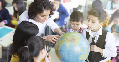 female teacher and students looking the globe