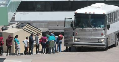 Migrants are loaded onto a bus at the Border Patrol Headquarters on Hondo Pass in El Paso